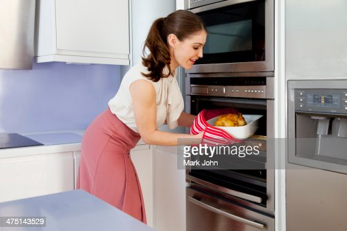 Young woman taking roasting dish out of oven