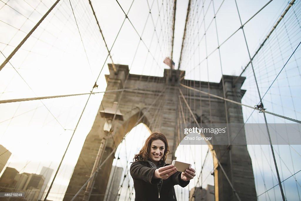 Young woman taking self portrait on Brooklyn bridge, New York, USA