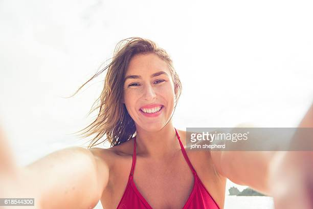 POV of young woman taking selfie at the beach.