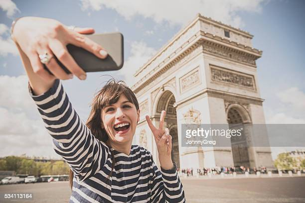 Young woman taking selfie by Arc de Triomphe