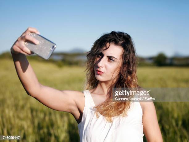 Young Woman Taking Selfie From Mobile Phone On Field