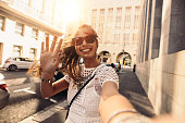 Tourist posing for a selfie in a street. Vlogger recording content for her travel vlog.