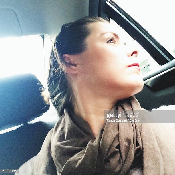 Young woman taking selfie in car