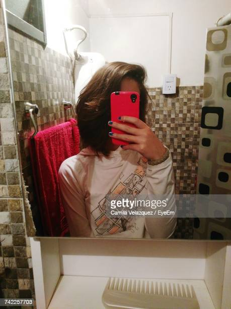 Young Woman Taking Selfie Through Mobile Phone Reflecting On Mirror In Bathroom