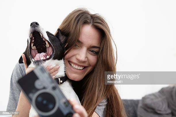 Young woman taking selfie with dog