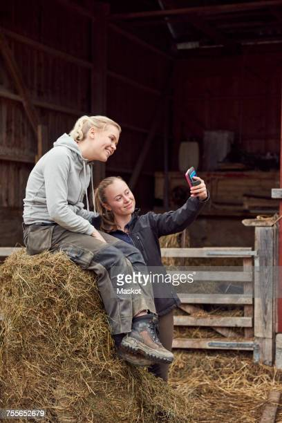 Young woman taking selfie with sister sitting on hay bale