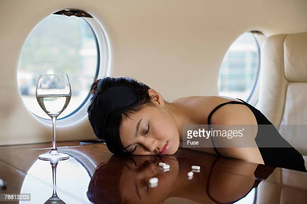 Young Woman Taking Sleeping Pills on Private Jet
