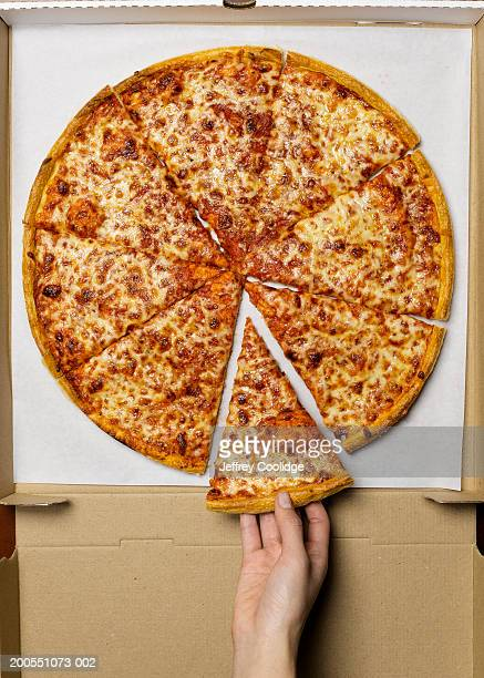 Young woman taking slice of pizza, overhead view