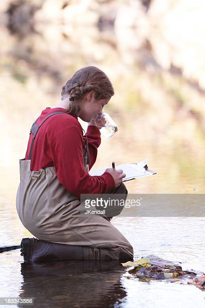 Young woman taking water sample in creek
