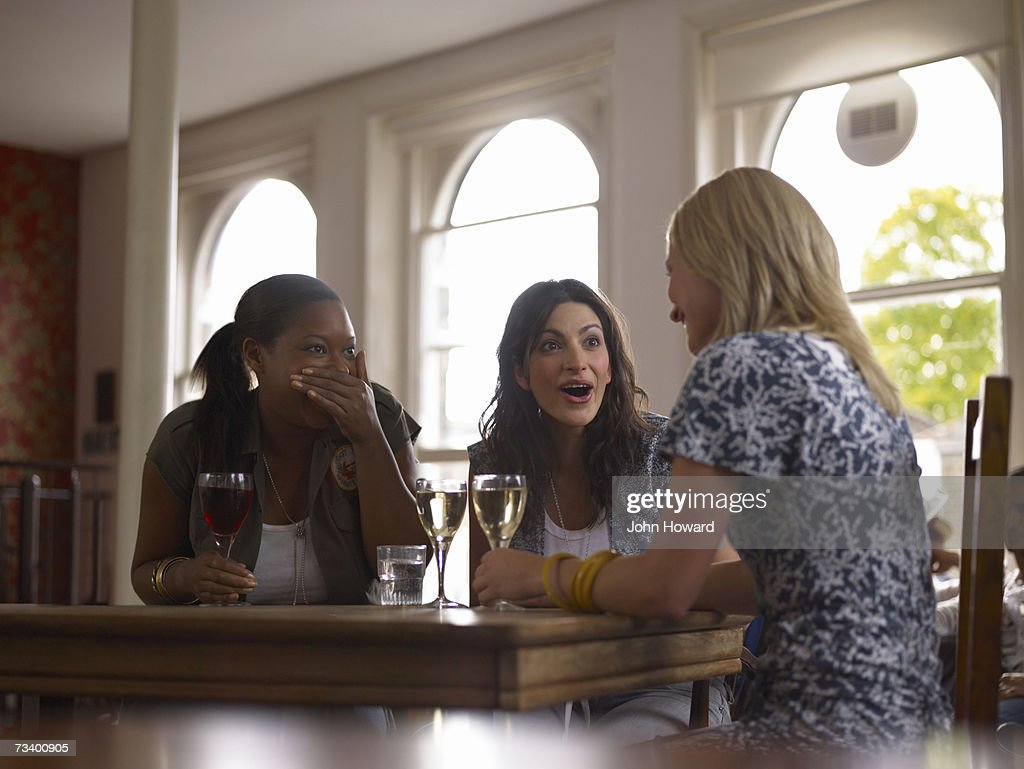 Young woman talking in pub, two friends gasping in response
