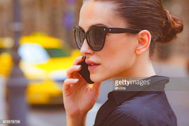Young woman talking on a mobile phone on the city street
