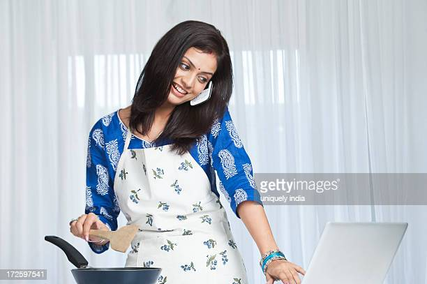 Young woman talking on cell phone and using a laptop while cooking