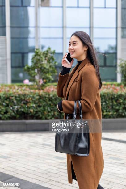 young woman talking on cellphone by office building