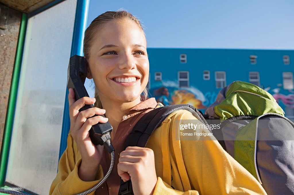 Young woman talking on payphone : Photo
