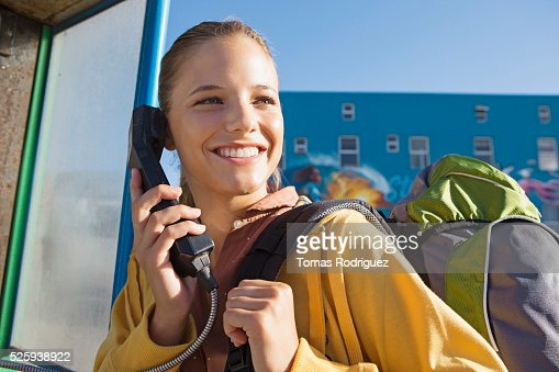 Young woman talking on payphone : Stock-Foto