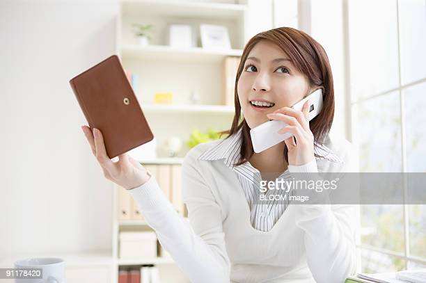 Young woman talking on phone, holding schedule book