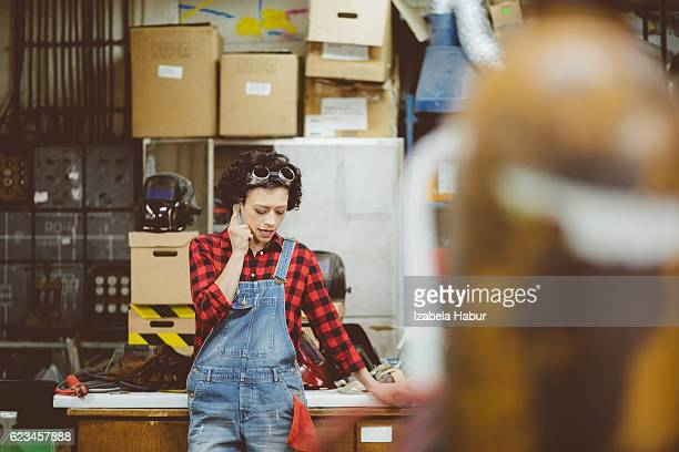 Young woman talking on phone in a workshop