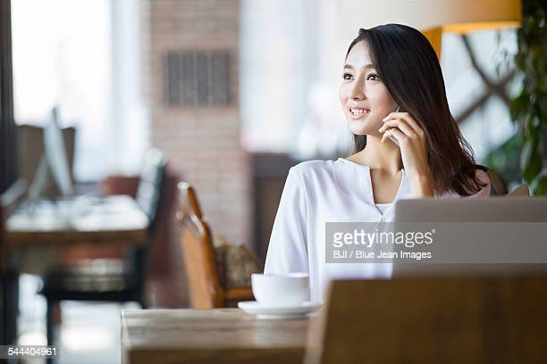 Young woman talking on phone in cafe