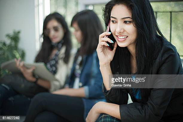 Young woman talking on phone in waiting room of office.