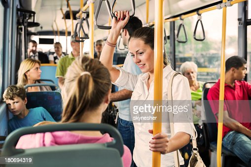 Young woman talking to her friend on bus.