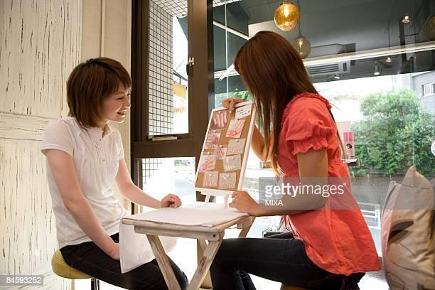 Young woman talking with beautician at  nail salon