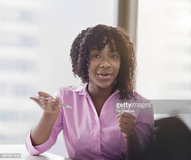 Young woman talking with colleague in office