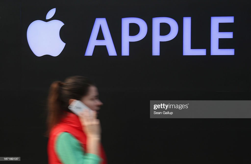 A young woman talks on an Apple iPhone as she walks past the construction site of the new Apple Store on Kurfuerstendamm avenue on April 22, 2013 in Berlin, Germany. The store is due to open in May and will the be the first Apple Store to open in the Germany capital.