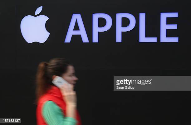 A young woman talks on an Apple iPhone as she walks past the construction site of the new Apple Store on Kurfuerstendamm avenue on April 22 2013 in...
