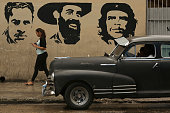 A young woman talks on her mobile phone as she walks past a mural depicting Cuban Comunist Party founder Julio Antonio Mella and Cuban revolutionary...