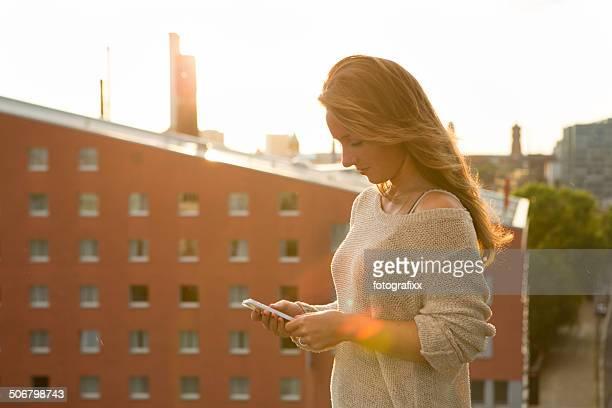 Junge Frau nutzt Ihr smartphone, Gegenlicht
