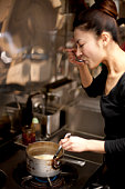 Young Woman Tasting at Kitchen in Restaurant