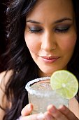 Young woman tasting margarita