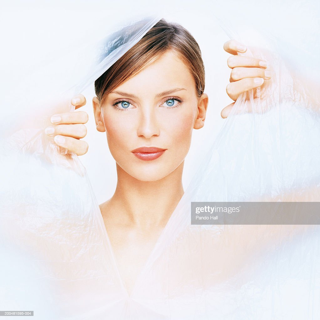 Young woman tearing hole in plastic, portrait : Stock Photo