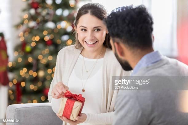 Junge Frau öffnet neckisch Freundes Weihnachtsgeschenk