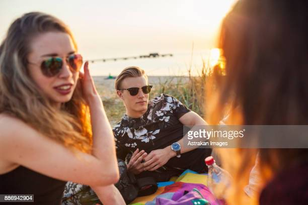 Young woman, teenage girl (16-17) and man talking on beach