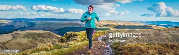 Young woman teenager trail running along mountain ridge path panorama
