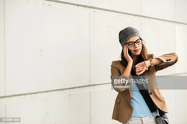 Young woman telephoning with smartphone while checking time