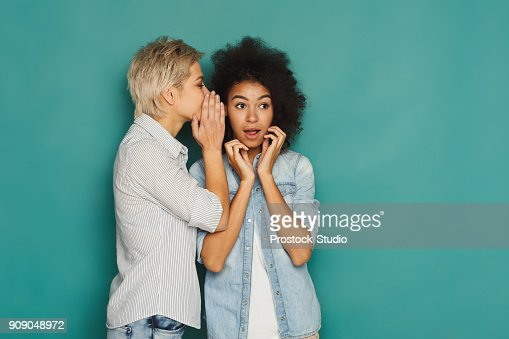 Young woman telling her friend some secrets : Stock Photo