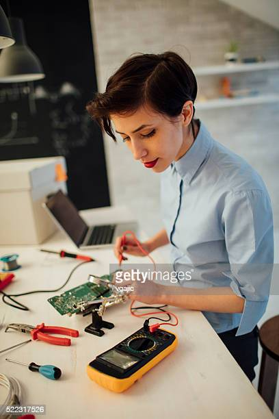 Young Woman Testing circuit board in her office.