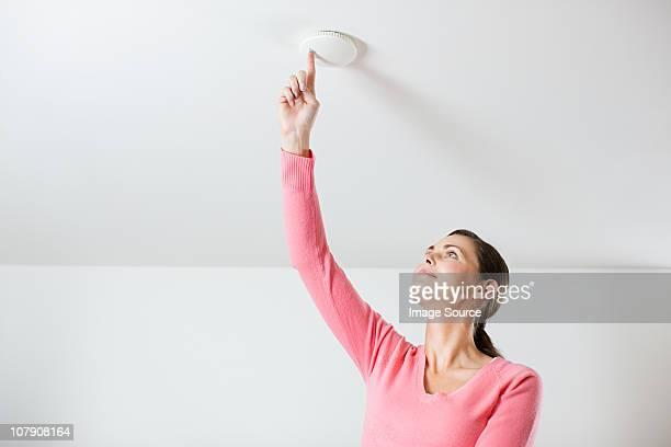 Jeune femme des tests Détecteur de fumée au plafond