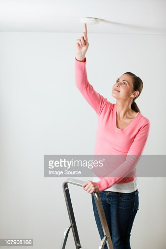 Young woman testing smoke alarm on ceiling