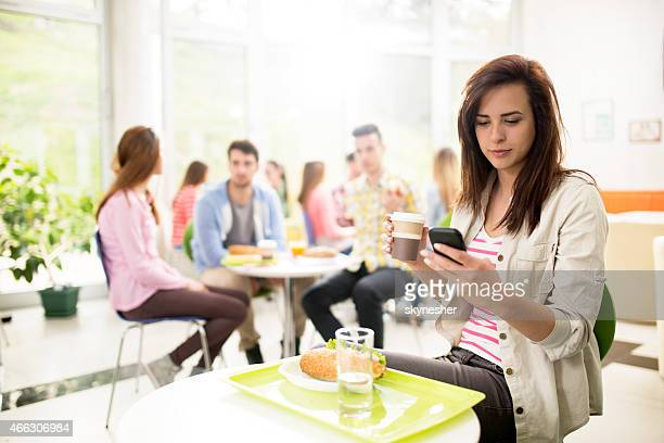 Young woman text messaging in cafeteria.