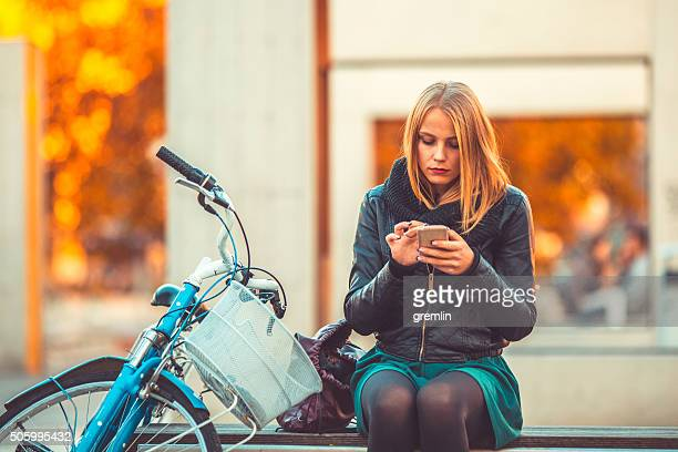 Young woman text messaging in the city