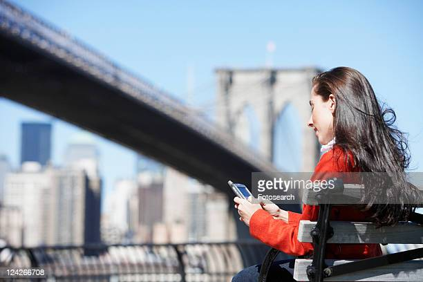 Young woman text messaging near Brooklyn Bridge, New York City, New York, USA