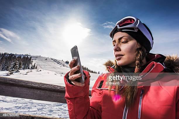 Jeune femme, envoi de SMS sur téléphone mobile de station de ski.