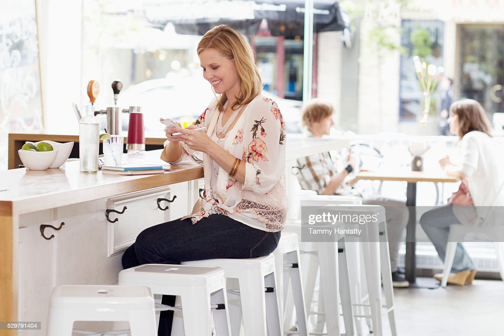 Young woman texting at bar counter : Photo