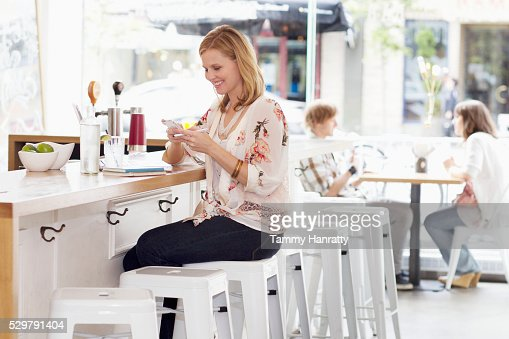 Young woman texting at bar counter : Stock Photo