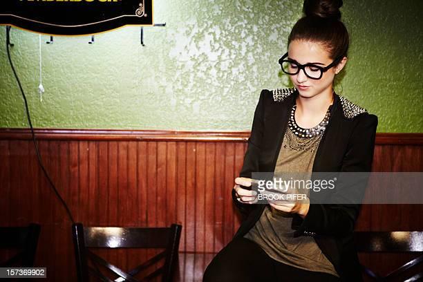 Young woman texting at bar