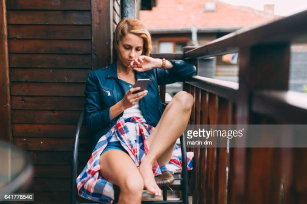 Young woman texting at the balcony