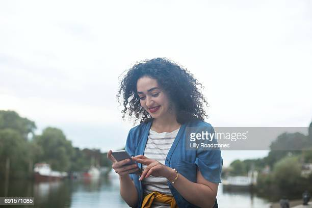 Young woman texting by the waterside